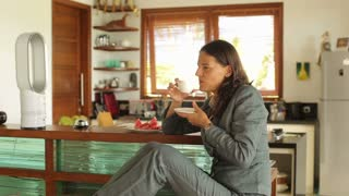 Relaxed businesswoman sitting in the kitchen and drinking coffee