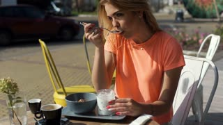 Relaxed girl eating yogurt for breakfast in the outdoor cafe, steadycam shot