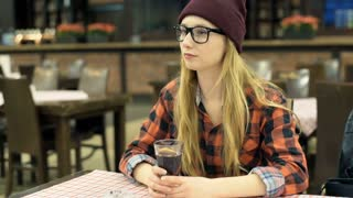 Relaxed, hipster girl sitting in the cafe and drinking beverage, steadycam shot