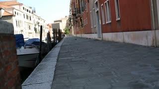 Rich man walking along canal in Venice, slow motion
