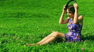 Romantic girl wearing headphones and listening music on the meadow