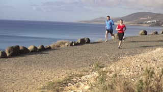 Runners while training on seashore, slow motion shot at 120fps