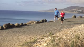 Runners while training on seashore, slow motion shot at 60fps