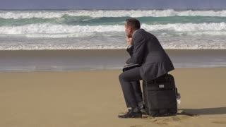 Sad businessman sitting on suitcase on the beach, slow motion shot at 240fps