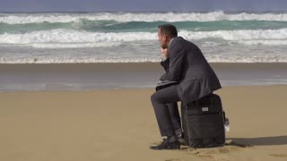 Sad businessman sitting on suitcase on the beach, slow motion shot at 60fps