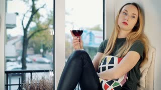 Sad girl drinking wine by the window and thinking about her problems
