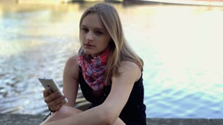Sad girl holding smartphone and thinking about something by the river