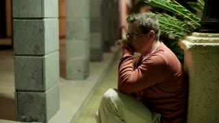 Sad man sitting alone at night garden