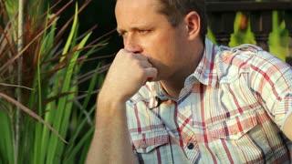 Sad man sitting in the garden
