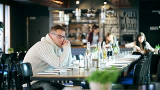 Sad man sitting in the restaurant and looking around