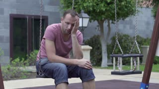 Sad man sitting on a swing, slow motion shot at 240fps