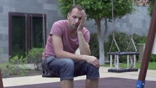 Sad man sitting on a swing, slow motion shot at 60fps