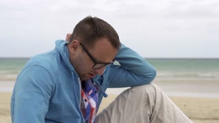 Sad man sitting on the beach, slow motion shot at 240fps