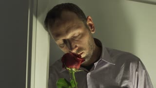 Sad man smelling rose and standing next to the window