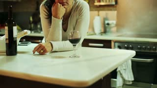 Sad woman drinking wine in the kitchen in the evening