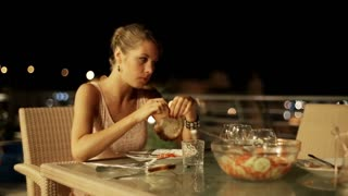 Sad woman eating dinner on the terrace at night, steadycam shot