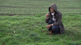 Sad woman in hood sitting on the grassland