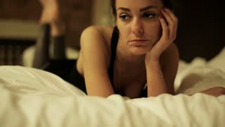 Sad woman lying on bed at night and looking to camera, steadycam shot.