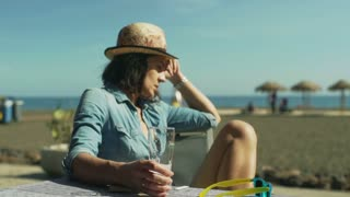 Sad woman sitting in the cafe on the beach and looking thoughtful, steadycam sho