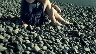 Sad woman sitting on the shingle beach and having problem, steadycam shot