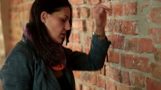 sad woman standing by the brick wall