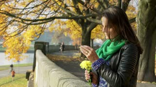 Sad woman standing on boulevard and playing with flower