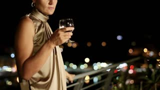 Sad woman with wine standing on the terrace at night, crane shot