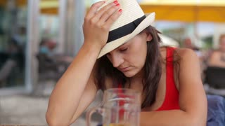 Sad young woman drinking beer in the restaurant, outdoors