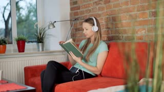 Satisfied girl listening music on headphones while reading book