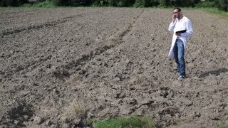 scientist talking on the cellphone and standing in the field