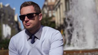 serious businessman sitting by a fountain, slow motion shot at 240fps
