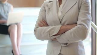 Serious looking businesswomen with crossed hands, interior