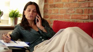 sick businesswoman lying on the sofa and using her cellphone