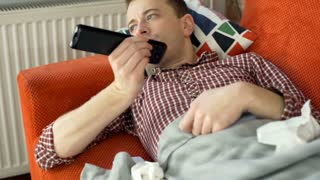 Sick man lying under blanket and watching television, steadycam shot