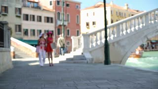 Smiling female friends walking with shopping bags, Venice, slow motion