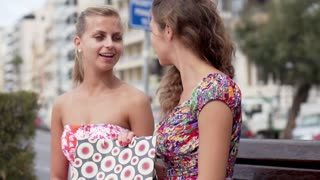 Smiling women after shopping sitting in the city, slow motion shot at 120fps