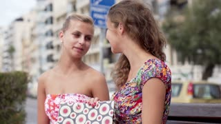 Smiling women after shopping sitting in the city, slow motion shot at 240fps