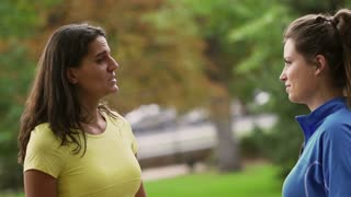 Sporty women chatting in the park, slow motion shot at 240fps, steadycam shot