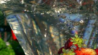 Strawberries falling into water, closeup, slow motion shot at 240fps