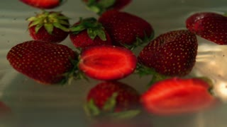 Strawberries spinning in water, closeup, slow motion shot at 240fps