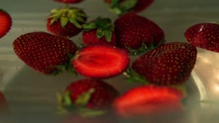 Strawberries spinning in water, closeup, slow motion shot
