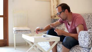 Stressed man doing his finances with tablet computer at home