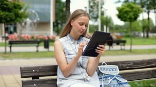 Student browsing internet on tablet and smiling to the camera