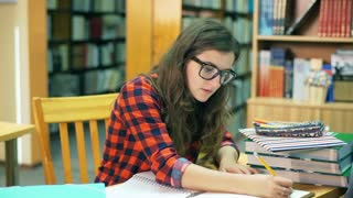 Student doing homework in the librarz and smiling to the camera