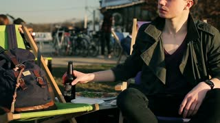 Student drinking beer in outdoor bar and relaxing