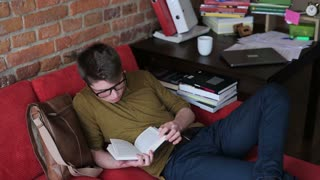 Student finish reading book and taking a nap on red sofa