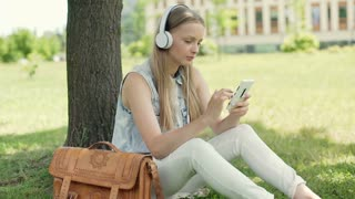 Student listening music and texting on smartphone while sitting on grass