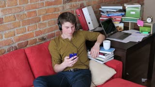Student listening music on headphones and sitting on red sofa