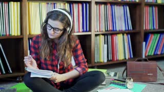 Student looking thoughtful and listening music in the library