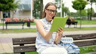 Student sitting on the bench and doing homework in her notebook